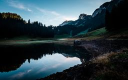 Amazing water reflection in clear moutain lake during sunrise morning switzerland stock photos