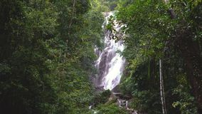 Amazing waterfall, falling water, lush green leaves is waving by the wind. Thailand stock footage