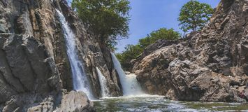 Amazing waterfall on the hard brown rock in a countryside jungle in a beautiful sunny day with green trees royalty free stock photo