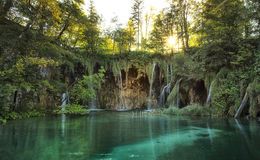 Amazing waterfall lagoon in Plitvice Lakes National Park. Many waterfalls located in green lagune, with sun star in top Stock Photos