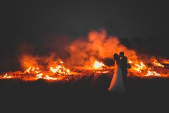 Amazing wedding couple near the fire at night Stock Images