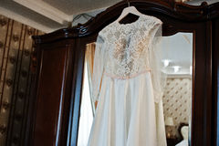 Amazing wedding dress on hangers at wooden closet on room of bri Royalty Free Stock Photos