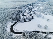 Amazing wild river in frozen forest. Really snowly winter on the north. Aerial panoramic view Royalty Free Stock Images