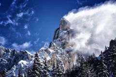 Amazing winter weather, blue sky and clouds coming of the rocks Stock Image