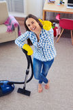 Amazing woman holding vacuum cleaner and showing clearness of ca Stock Photos