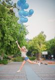Amazing woman let many blue balloons in the sky royalty free stock photo