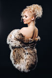 Amazing woman in lynx fur coat in mirrored sun glasses, a chic fur coat. Portrait of a woman in Studio on a black Stock Image