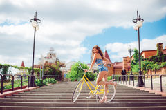 Amazing woman posing near bicycle, fashion model in clothes. royalty free stock photography