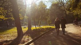 Amazing woman in a yellow dress and black coat, with a handsome man in elegant autumn wear. Luxurious young couple stock video footage