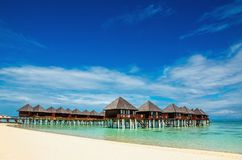 Amazing wooden bungalow on turquoise water Royalty Free Stock Photo