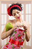 Amazing young brunette pinup lady with needlwork. Portrait of amazing funny young brunette pinup lady with knitting tread smiling looking at her needlwork over Stock Photo