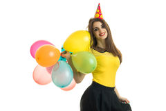 Amazing young girl in a bright dress smiles and holds in her hand a lot of hot air balloon Royalty Free Stock Images