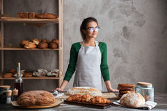 Amazing young lady baker standing at bakery near bread. Picture of amazing young lady baker standing at bakery near bread. Looking aside stock photos