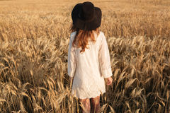 Amazing young lady in the field. Looking aside. Back view image of amazing young lady in the field. Looking aside stock images