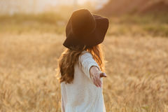Amazing young lady in the field. Looking aside. Back view image of amazing young lady in the field. Looking aside stock photography
