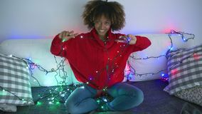 Coquettish model in sweater with twinkle lights. Amazing young model looking playfully at camera while posing in cozy red sweater on sofa and holding lights of stock video footage