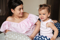 Amazing young mother lies on bed with her little daughter Stock Photos