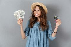 Amazing young pretty woman holding money and credit card. Image of amazing young pretty woman standing over grey wall wearing hat holding money and credit card Royalty Free Stock Photography