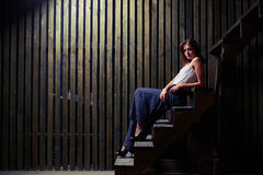 Amazing young stylish woman sitting on stairs and looking at cam Royalty Free Stock Images