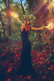 Amazing young witch casts a spell in the woods. Outdoors Royalty Free Stock Photos