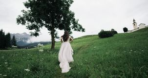 Amazing young woman with pretty long dress running in the middle of green field