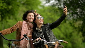 Amazing Young Women with Bicycles are Making Selfie Using Mobile Phone. Portrait of Two Smiling Dark-haired Female stock footage