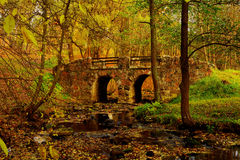 Amazingly beautiful old, ancient bridge in a park or forest Royalty Free Stock Image
