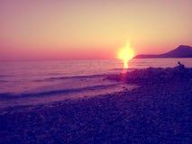 Amazng orange solnedgång, strand och berg Arkivbild