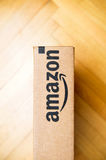 Amazon Box seen from above. PARIS, FRANCE - JAN 28, 2016: Horizontal view of Amazon logotype printed on cardboard box side, seen from above on a wooden floor stock photos