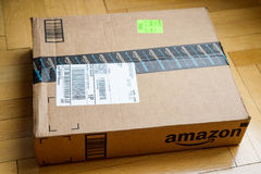 Amazon Box on wooden floor. PARIS, FRANCE - JAN 28, 2016: Amazon Prime lPremium box seen from above on a wooden floor. Amazon Inc is the an American electronic e stock images