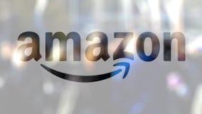 amazon com logo na szkle przeciw zamazanemu tłumowi na steet Redakcyjny 3D rendering zbiory