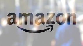 amazon com logo na szkle przeciw zamazanemu tłumowi na steet Redakcyjny 3D rendering Fotografia Royalty Free