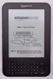 Amazon Kindle E-Reader. An Amazon Kindle ereader with the opening screen message which is quite often mistaken for a sticker on front of the screen, given the Stock Photo