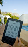 Amazon Kindle E-Reader. An amazon kindle ereader being used poolside in bright sunlight.  This clearly demonstrates the e-ink anti glare technology which enables Royalty Free Stock Photo