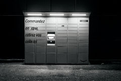 Amazon Locker black and white. PARIS, FRANCE - FEB 15, 2017: Black and white night view over an Amazon locker orange delivery package locker at dusk - Amazon Stock Photos