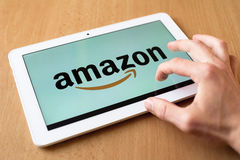 Amazon. Man's hand use with his fingers tablet. Amazon app is on the screen. Amazon is popular retailer with various kinds of goods