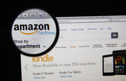 Amazon. Photo of Amazon homepage on a monitor screen through a magnifying glass Stock Photo