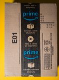 Amazon Prime cardboard box delivery with seal scotch tape. PARIS, FRANCE - SEP 28, 2018: New Amazon Cardboard box against yellow background with seal scotch tape royalty free stock photos