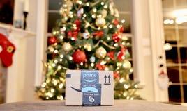 Amazon Prime Christmas Holiday Gift. An Amazon prime Christmas holiday present sits in front of a Christmas Tree stock image