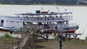 The amazon rain forest and river as tourists get on to boat. Tourists on a boat in the Amazon river stock footage