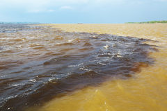 Amazon & Rio Negro waters not mixing, Brazil. The Meeting of Waters, close to Manaus, is the famous confluence between Rio Negro, a river with very dark Royalty Free Stock Photos