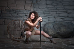 Amazon in the skin. The girl sat leaning on a sword she Amazon dressed in skins stock image