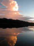 Amazon sky. Cloud formations over black water oxbow lake in the Amazon jungle, at sunset Stock Image