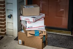 Amazon and USPS Packages Delivered. Lancaster, PA, USA - December 15, 2017: USPS Priority Mail boxes, Amazon, and other packages delivered at a residential home stock image