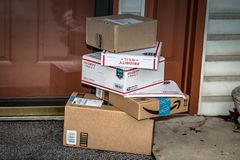 Amazon and USPS Packages. Lancaster, PA, USA - December 15, 2017: USPS Priority Mail boxes, Amazon, and other packages delivered at a residential home front door royalty free stock image