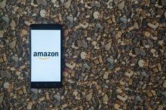 Amazonas-Logo auf Smartphone auf Hintergrund von kleinen Steinen Lizenzfreie Stockfotos