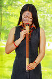 Amazonian exotic woman with facial paint and black dress, blowing into blowgun, forest background Royalty Free Stock Image