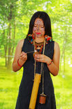 Amazonian exotic woman, facial paint, black dress, case for arrows and small wooden bottle hanging around neck, applying Stock Image