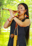 Amazonian exotic woman, facial paint, black dress, case for arrows and small wooden bottle hanging around neck, blowing Stock Photo