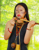 Amazonian exotic woman, facial paint, black dress, case for arrows and small wooden bottle hanging around neck, loading Stock Image